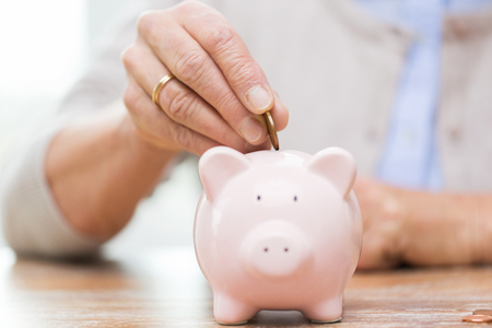 retirement age: savings, money, annuity insurance, retirement and people concept - close up of senior woman hand putting coin into piggy bank Stock Photo