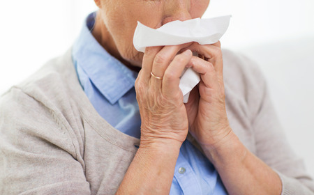 health care, flu, hygiene, age and people concept - close up of sick senior woman blowing nose to paper napkin at home