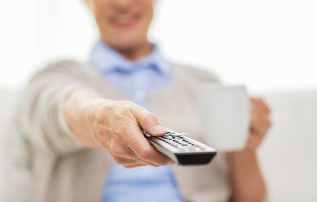 technology, television, age and people concept - close up of senior woman watching tv, drinking tea and changing channels by remote control at home