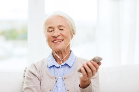 people relaxing: technology, age and people concept - happy senior woman with smartphone and earphones listening to music at home Stock Photo