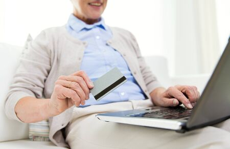 compute: technology, age and people concept - close up of happy senior woman with laptop compute and credit or bank card r at home
