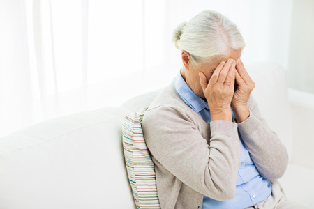 grief: health care, pain, stress, age and people concept - senior woman suffering from headache or grief Stock Photo