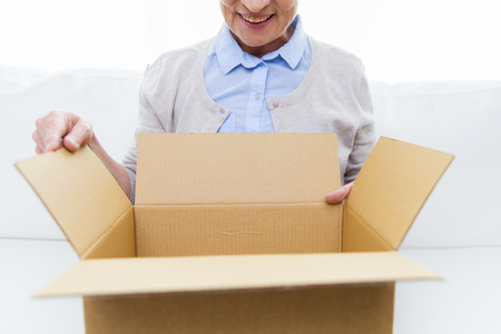 age, delivery, mail, shipping and people concept - close up of happy smiling senior woman looking into open parcel box at home Stock Photo