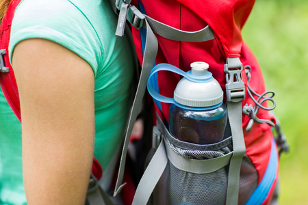 travel, tourism, hike and people concept - close up of woman with water bottle in backpack pocket