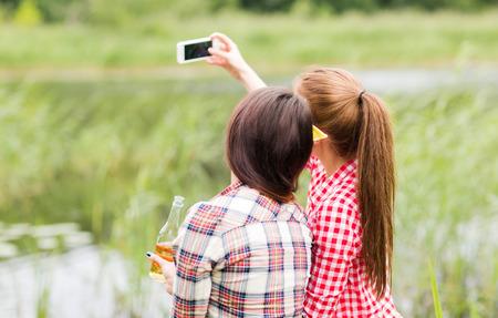mujeres de espalda: camping, viajes, turismo, caminata y concepto de las personas - mujeres jóvenes felices con las botellas de vidrio beber sidra o cerveza y teniendo autofoto por teléfono inteligente al aire libre de la parte posterior Foto de archivo