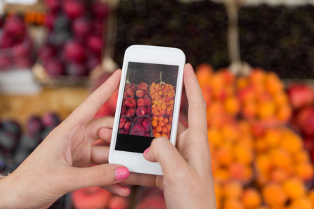 sale, shopping, food, technology and people concept - close up of hands with smartphone taking picture of fruits at street market Stock Photo