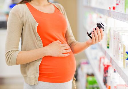 health: 임신, 의학, 약학, 보건 의료 사람들 개념 - 가까운 임신 한 여자 독서 라벨의 최대 약국에서 약 항아리에