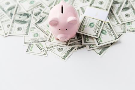 Negocios, las finanzas, la inversión, el ahorro y la corrupción concepto - cerca de dólar de dinero en efectivo y una hucha en la mesa Foto de archivo - 47563978
