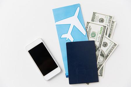 cash: el turismo, los viajes y los objetos concepto - pasaje aéreo, dinero, teléfonos inteligentes y el pasaporte en la mesa
