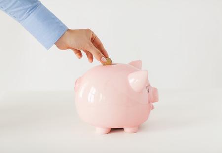 zaken, financiën, investering, geldbesparing en begrotingsconcept - sluit omhoog van hand die muntstuk zetten in spaarvarken