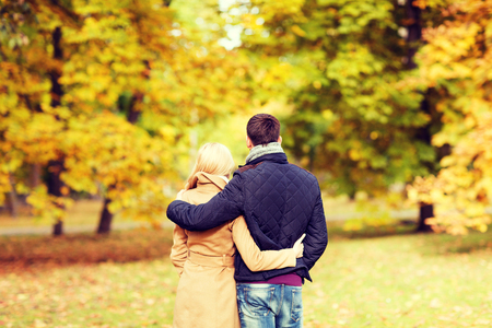 autumn in the park: love, relationship, family and people concept - couple hugging in autumn park from back