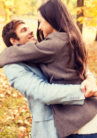 love park: love, relationship, family and people concept - smiling couple hugging in autumn park Stock Photo