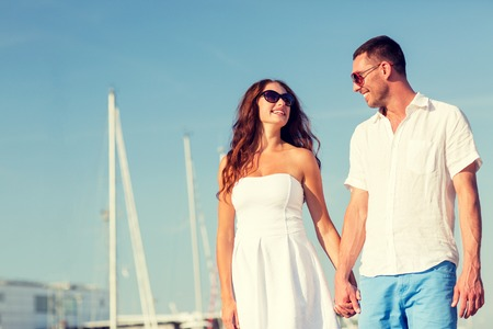 happy couple: love, travel, tourism, sailing, people and friendship concept - smiling couple wearing sunglasses walking at harbor Stock Photo