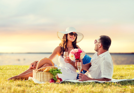 anniversary beach: love, dating, people and holidays concept - smiling couple drinking champagne on picnic over evening seaside background