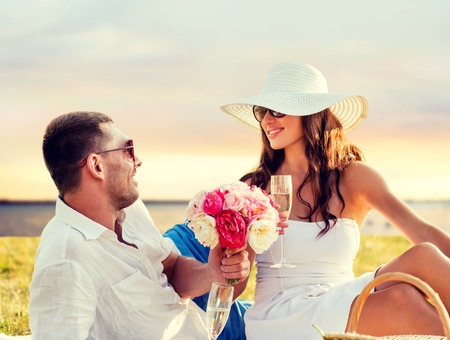 latin couple: love, dating, people and holidays concept - smiling couple drinking champagne on picnic over seaside sunset background Stock Photo