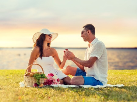 proposal of marriage: love, dating, people, proposal and holidays concept - smiling young man giving small red gift box with wedding ring to his girlfriend on picnic over seaside sunset background