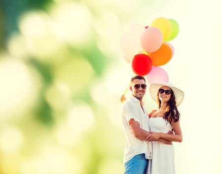 happy couple white background: love, wedding, summer, dating and people concept - smiling couple wearing sunglasses with balloons hugging over green background