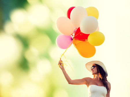 happy woman: happiness, summer, holidays and people concept - smiling young woman wearing sunglasses with balloons over green background Stock Photo