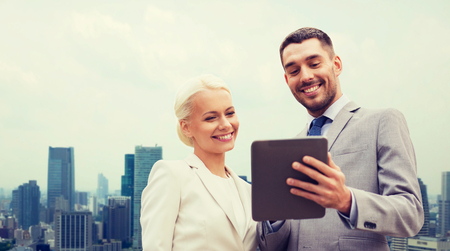 business, partnership, technology and people concept - smiling businessman and businesswoman with tablet pc computer over city background
