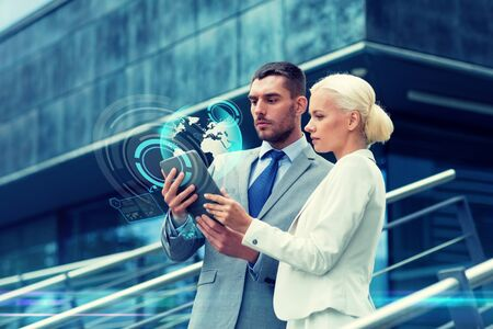 partnership: business, partnership, technology and people concept - businessman and businesswoman working with tablet pc computer and globe hologram on city street Stock Photo