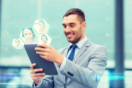 business, online communication, technology and people concept - smiling businessman making video call with tablet pc computer on city street
