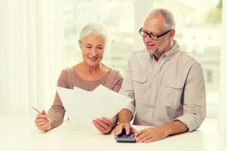 ahorros: familia, los negocios, el ahorro, la edad y el concepto de la gente - sonriente pareja senior con documentos y calculadora en casa