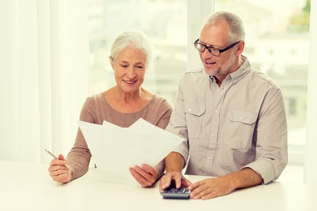 family, business, savings, age and people concept - smiling senior couple with papers and calculator at home Banque d'images
