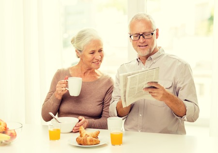 alimentos y bebidas: family, technology, food, drinks and people concept - happy senior couple having breakfast and reading newspaper at home