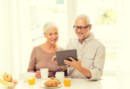 food and drinks: family, technology, food, drinks and people concept - happy senior couple with tablet pc computer having breakfast at home