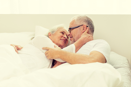 age: family, bedtime, resting, age and people concept - happy senior coupler lying in bad at home Stock Photo