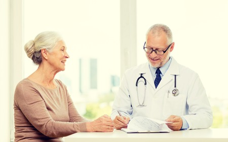 mature women: medicine, age, health care and people concept - smiling senior woman and doctor meeting in medical office