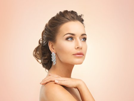 close up of beautiful woman wearing shiny diamond earrings