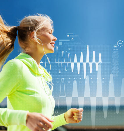 rate: sport, fitness, exercise and lifestyle concept - smiling woman doing running with earphones outdoors Stock Photo