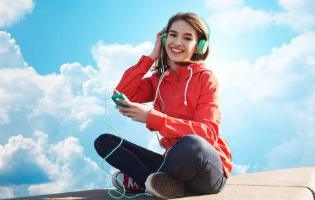 lady on phone: technology, music and people concept - smiling young woman or teenage girl with smartphone and headphones listening to music outdoors over blue sky and clouds background