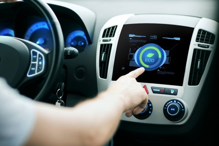 body parts: transport, modern, green energy, technology and people concept - male hand using car eco system mode Stock Photo