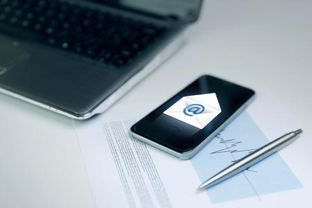 Negocio, la tecnología y el concepto de comunicación - cerca de smartphone con icono de mensaje de correo electrónico, ordenador portátil y un gráfico con la pluma en la mesa de la oficina Foto de archivo - 47564190