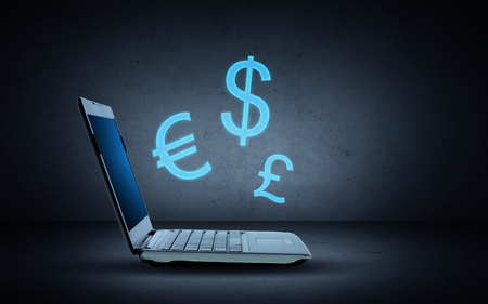 desktop background: technology, finances and exchange rate concept - open laptop computer with blue lighting currency symbols over dark gray background