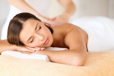 therapy: health, beauty, resort and relaxation concept - beautiful woman with closed eyes in spa salon getting massage