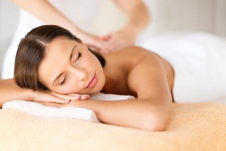 la salud, la belleza, la estación y el concepto de relajación - hermosa mujer con los ojos cerrados en salón del balneario que consigue masaje Foto de archivo