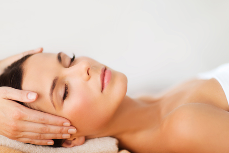 spa treatment: spa, resort, beauty and health concept - beautiful woman in spa salon getting face treatment
