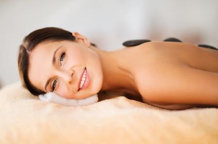 is hot: salud y belleza, centro tur�stico y la relajaci�n concepto - mujer hermosa en el sal�n de spa con piedras calientes
