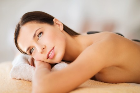 health beauty: health and beauty, resort and relaxation concept - beautiful woman in spa salon with hot stones