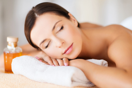 woman in spa: beauty and spa concept - happy woman in spa salon lying on the massage desk Stock Photo