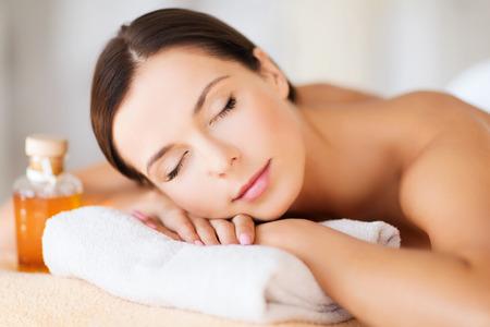 szépség: szépség és spa koncepció - boldog nő spa szalon fekvő masszázs asztalon