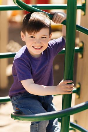 zomer, jeugd, vrije tijd en mensen concept - gelukkig jongetje op kinderspeelplaats klimrek