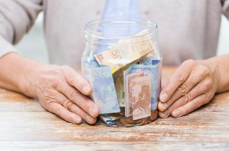 seguro: ahorros, dinero, seguro de renta vitalicia, la jubilación y la gente concepto - cerca de la mujer mayor manos con el dinero en frasco de vidrio
