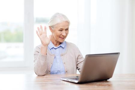 personas saludando: la tecnología, la edad, el gesto, la comunicación y el concepto de la gente - la mujer mayor feliz con el ordenador portátil que tiene el chat de vídeo en casa y agitando la mano Foto de archivo