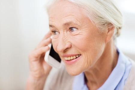technologie, communicatie leeftijd en mensen concept - gelukkig senior vrouw met smartphone belt thuis Stockfoto