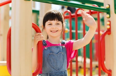 summer, childhood, leisure, gesture and people concept - happy little girl waving hand on children playground climbing frame Stock Photo