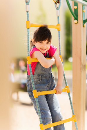 climbing frame: summer, childhood, leisure and people concept - happy little girl on children playground climbing by rope-ladder